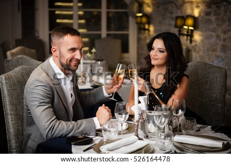 romantic relationship concept - couple with champagne glasses dating and toasting in restaurant