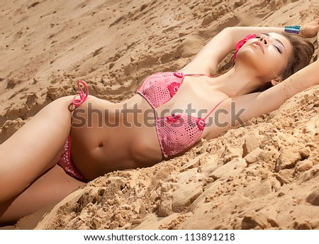 Romantic relaxed woman in bikini on sand sunbathing and resting