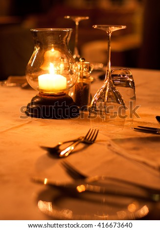 Romantic restaurant table setting of cutlery and glasses - stock photo