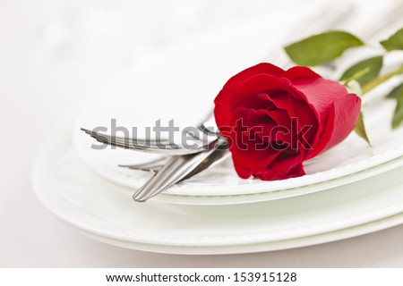 Romantic restaurant table setting with red rose on plates - stock photo