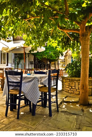 Romantic restaurant under the tree. Vourliotes village main square, Samos, Greece.  - stock photo