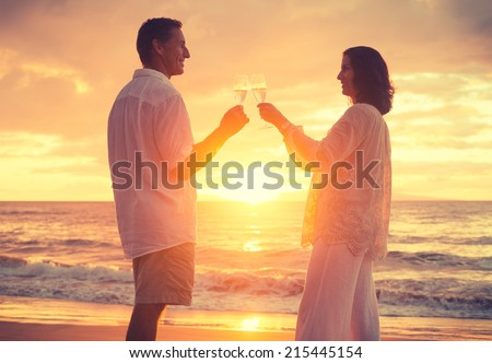 Romantic Retired Couple Drinking Champagne to Celebrate on Vacation  - stock photo