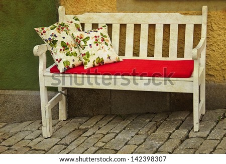 romantic rustic wooden bench with pillows outdoor against yellow wall