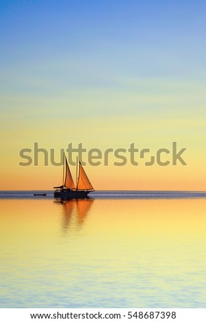 Romantic sailing boat reflected in tropical ocean at twilight.