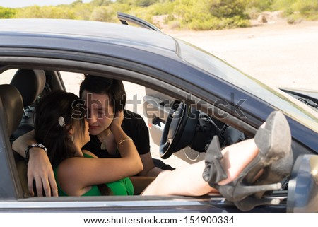 Romantic scene with a young couple inside a car - stock photo