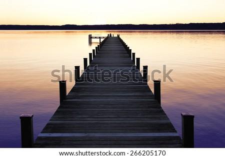 romantic scenery at starnberg lake, with boardwalk at sunset - stock photo