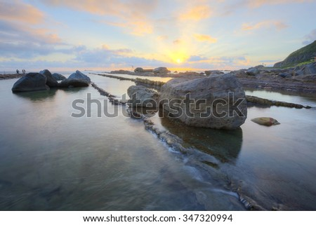 Romantic scenery of dawning sky by rocky seashore in northern Taiwan (long exposure effect) with beautiful reflections of golden sun light on tranquil sea water - stock photo