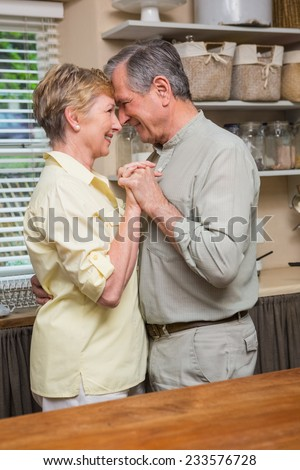 Romantic senior couple dancing together at home in the kitchen - stock photo