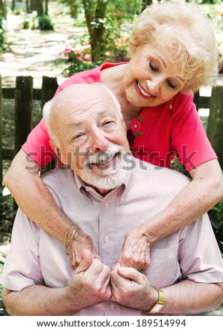 Romantic senior couple in love.  Wife is embracing the husband.