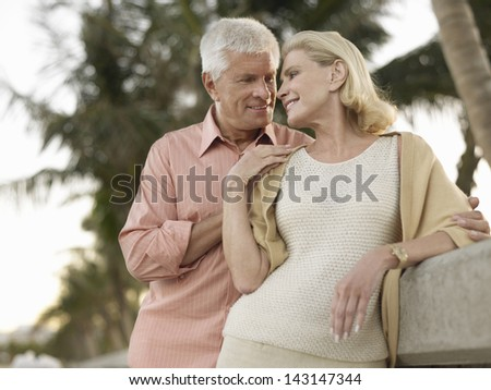Romantic senior couple looking at each other on tropical beach - stock photo