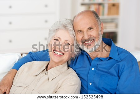 Romantic senior couple sitting close together on a sofa in the house smiling happily at the camera - stock photo