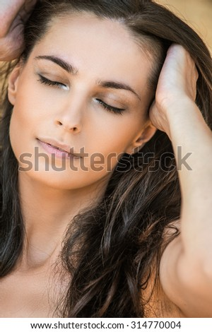 romantic sexy beautiful woman holds hair arm - stock photo