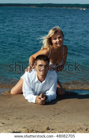romantic slavonic couple - blonde girl in peignoir and brown haired man in white shirt taking their time on the beach - stock photo