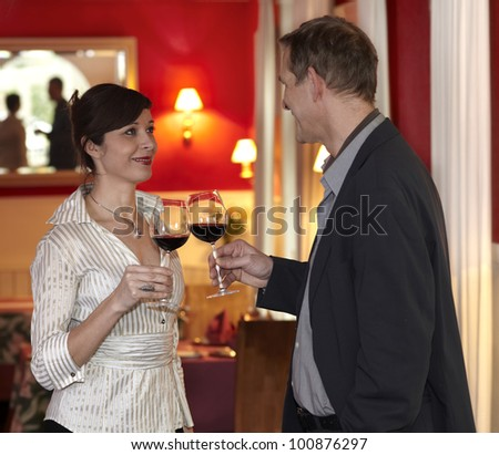 Romantic smiling couple toasting each other with red wine in a plush red interior