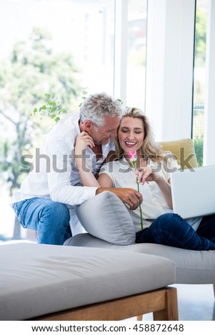 Romantic smiling mature couple with rose at home - stock photo