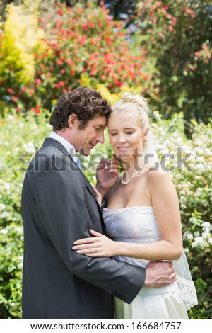 Romantic smiling newlyweds embracing in the countryside