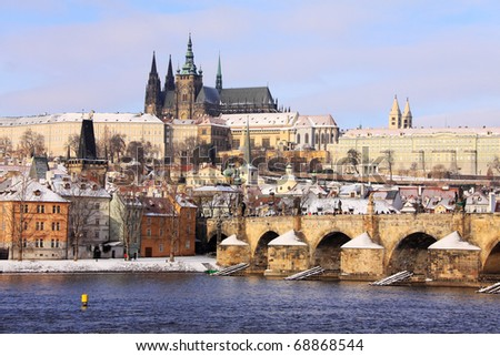 Romantic Snowy Prague, gothic Castle with the Charles Bridge in the sunny Day