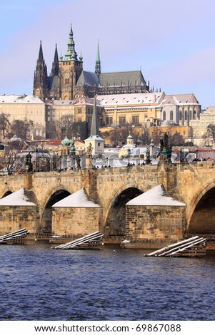 Romantic Snowy Prague gothic Castle with the Charles Bridge in the sunny Day