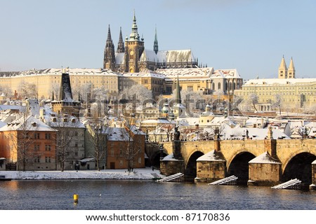Romantic Snowy Prague gothic Castle with the Charles Bridge in the sunny Day,  Czech Republic