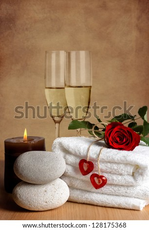 Romantic spa decoration with candles, spa stones, rose and champagne on a vintage background