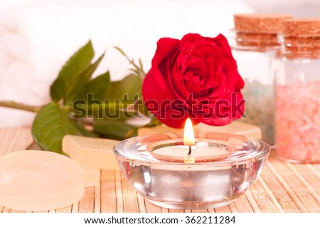 Romantic spa getaway with rose, candle, soaps, bath salt and towels background  - stock photo