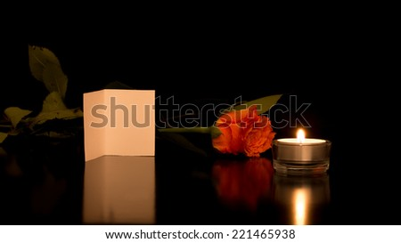 Romantic Still Life of Blank Card with Rose and Candle on Shiny Black Surface. - stock photo