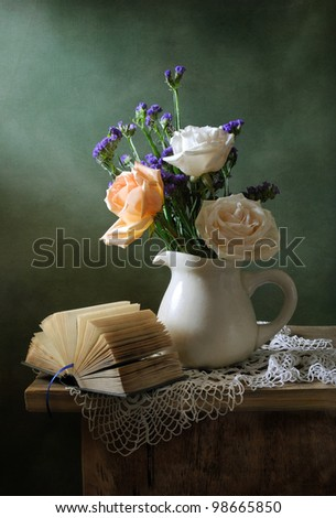 Romantic still life with a bouquet of roses and a book - stock photo
