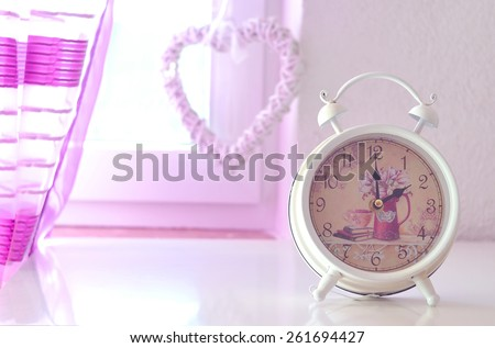 Romantic still life with alarm clock in the foreground a pink curtain and heart in the background