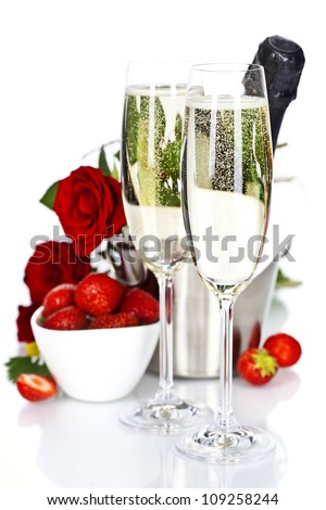 Romantic still life with champagne, strawberry and beautiful red roses over white - stock photo