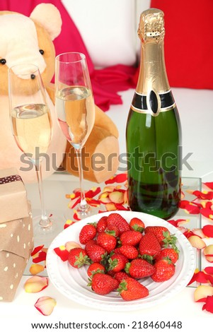 Romantic still life with champagne, strawberry and petals of roses close-up - stock photo