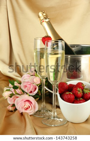 Romantic still life with champagne, strawberry and pink roses, on color fabric background - stock photo