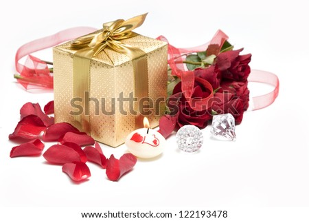 Romantic still life with gift, candle and roses
