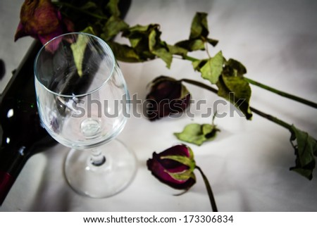 Romantic still life with wine and beautiful red roses.