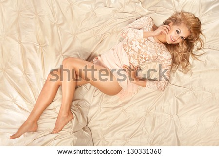 Romantic style photo of sensual blonde smiling beauty relaxing in big bed. Long curly hair. - stock photo