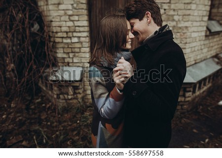 romantic stylish couple hugging gently and smiling in autumn park. man and woman embracing, showing true feelings. family togetherness concept
