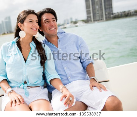 Romantic summer couple in a boat looking very happy