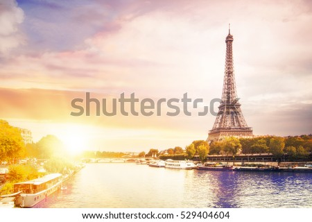 Romantic sunset background. Eiffel Tower with boats on Seine river in Paris, France.