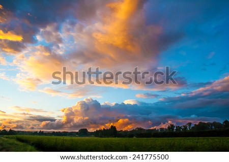 Romantic sunset sky with fluffy clouds. - stock photo