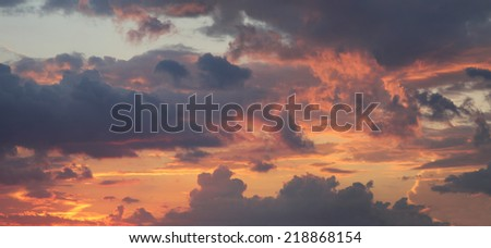 romantic sunset sky with illuminated clouds in orange pink and yellow - stock photo