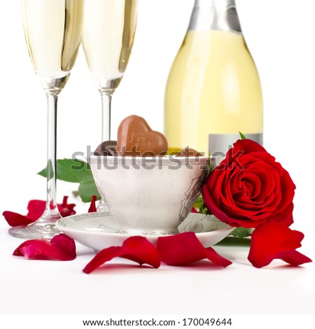 Romantic table decoration with rose petals, champagne and chocolates - stock photo