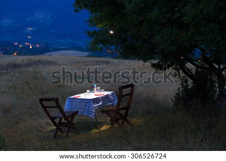 romantic table for two in full moon night, fields in nature near high mountain town - stock photo