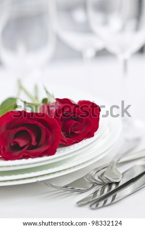 Romantic table setting for two with roses plates and cutlery - stock photo