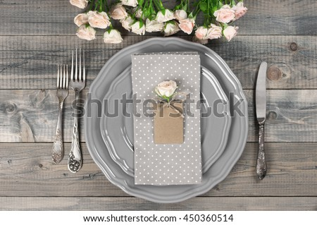 Romantic table setting in rustic style on wooden table: gray plates, vintage silverware, linen napkin, blank rough tag and rose flowers. Top view point.