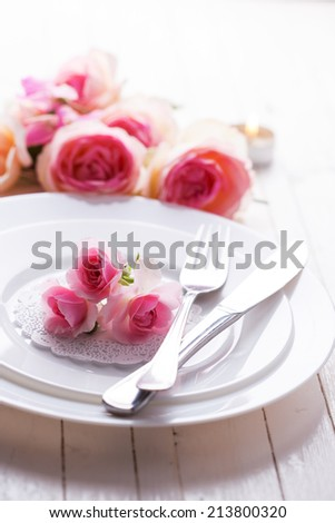 Romantic table setting. Roses on plate.  Selective focus. - stock photo