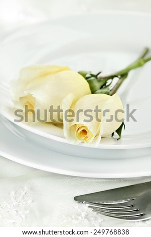Romantic table setting with long stem yellow roses. Extreme shallow depth of field with selective focus on rose in foreground. - stock photo