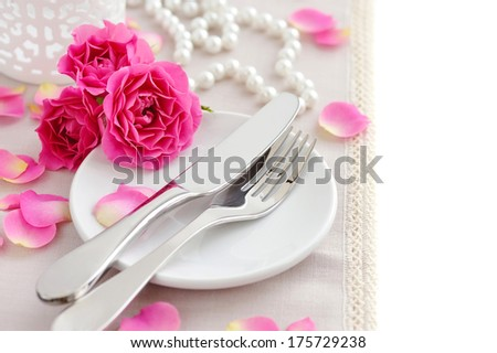 Romantic table setting with pink roses on a linen napkin - stock photo