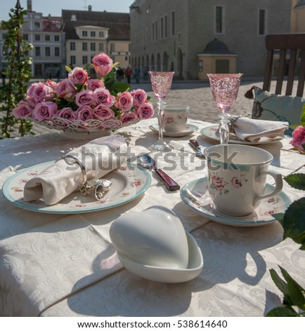 Romantic table setting with roses. Heart shaped porcelain box in foreground. Medieval city view on background.