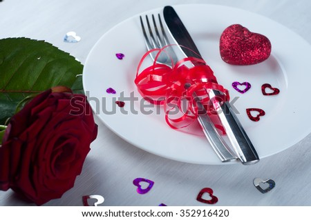 Romantic table setting with roses plates and cutlery - stock photo