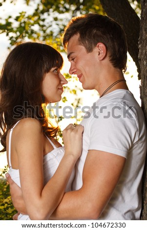 Romantic teenage couple by tree in park - stock photo