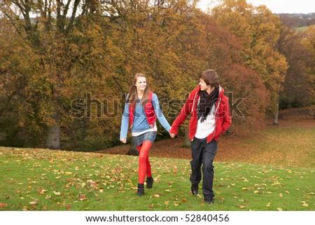 Romantic Teenage Couple Walking Through Autumn Landscape - stock photo